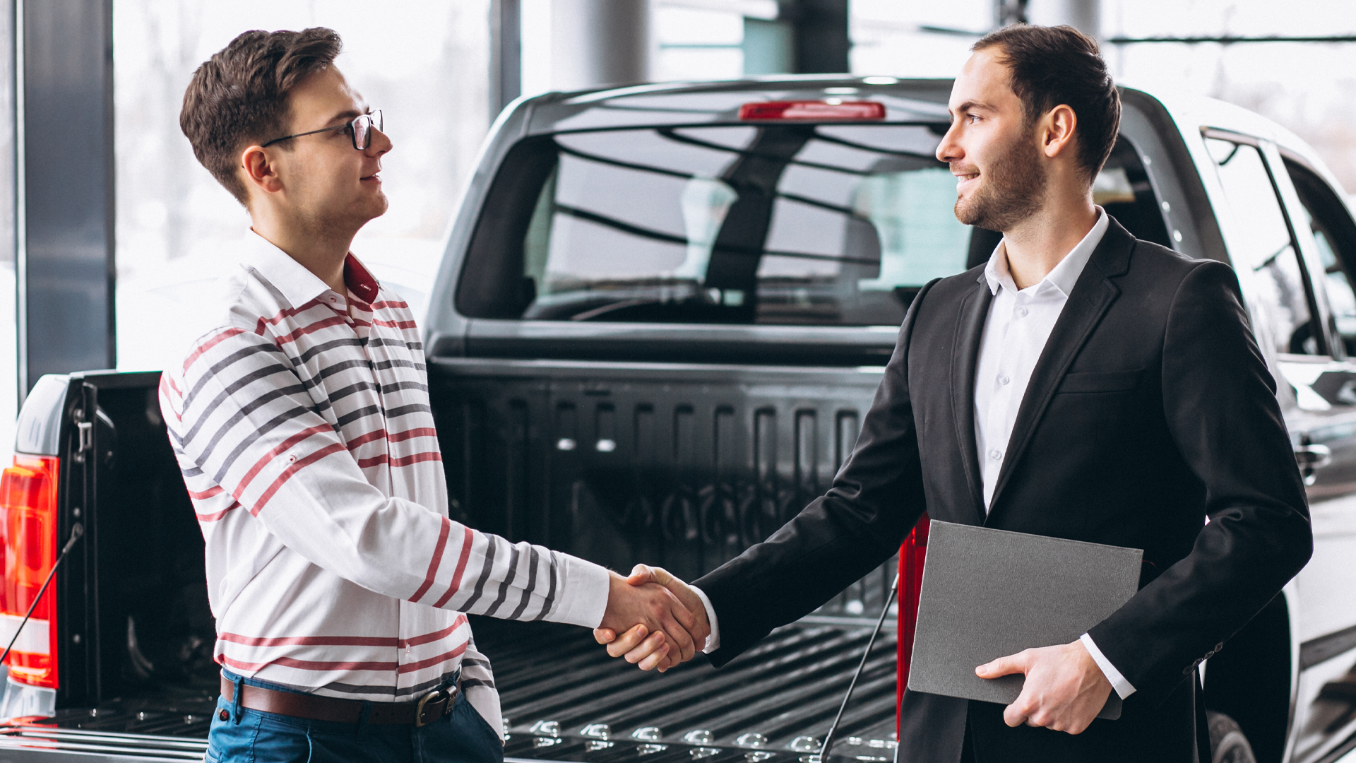 Two men shaking hands behind a truck.