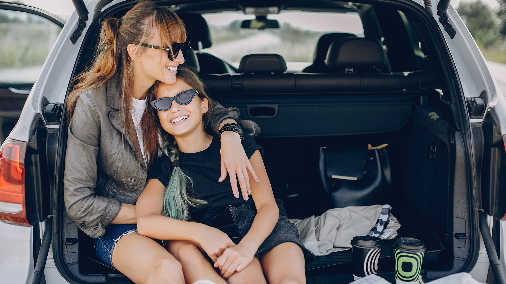 Woman and child sitting in the back of a car smiling.