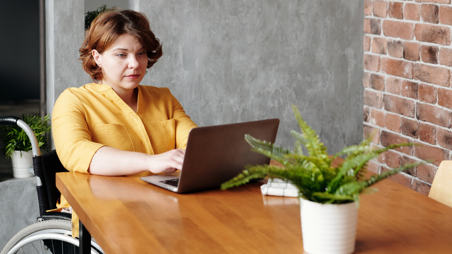 woman in wheelchair at laptop