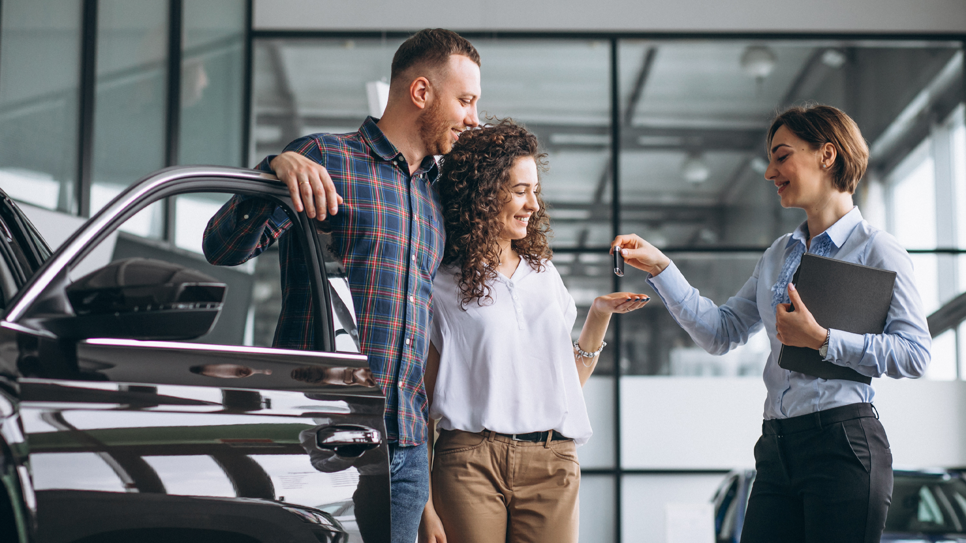 Man and woman receiving keys to a car at the dealership.