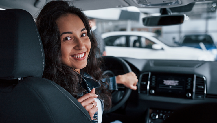 Woman backing up a car smiling.